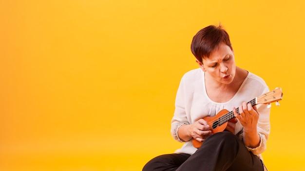 Cópia, espaço, mulher sênior, violão jogo