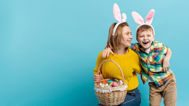 Cópia-espaço sorridente menino e mãe com ovos pintados