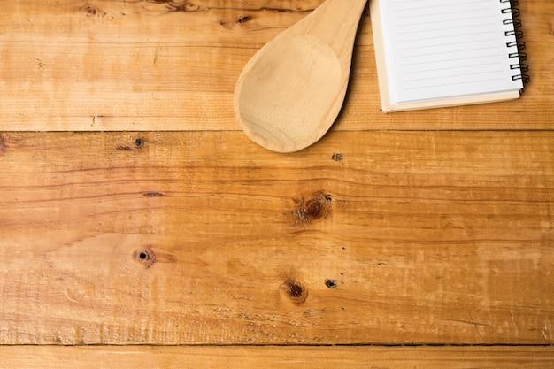 Copie a colher e o caderno do espaço no de madeira do marrom