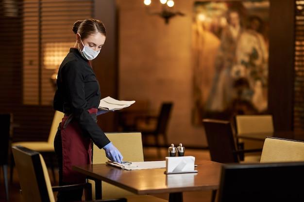 Copie a foto do espaço de uma senhora trabalhando em um restaurante e arrumando as mesas enquanto tece a máscara e as luvas
