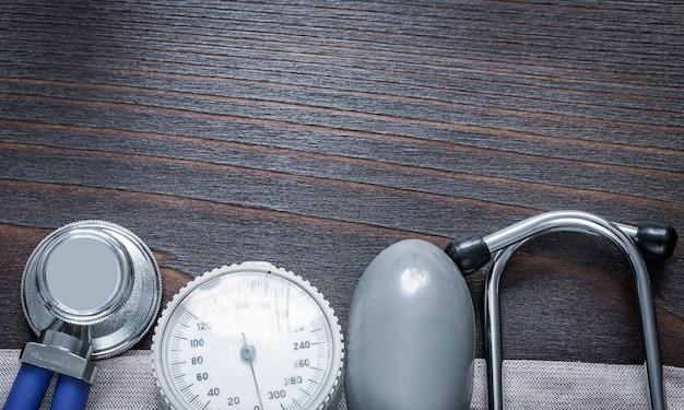 Copie a imagem do espaço do monitor do estetoscópio e da pressão arterial no conceito de medicina da placa de madeira vintage