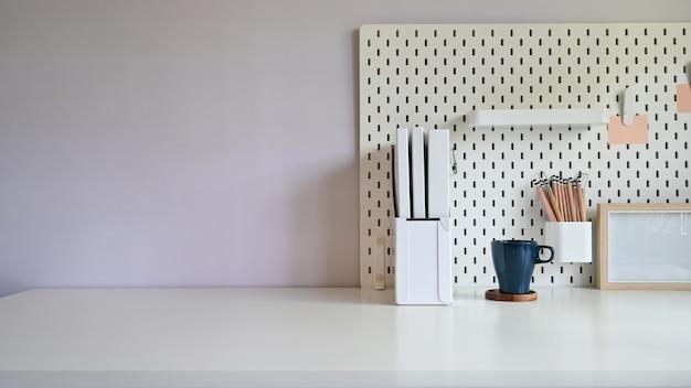 Copie a mesa de escritório de espaço com placa de arquivo de documento, café e peg com lápis na mesa.
