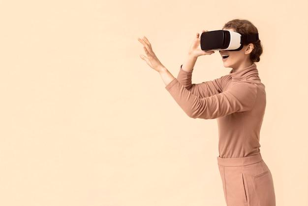 Copie a mulher do espaço brincando com um fone de ouvido de realidade virtual