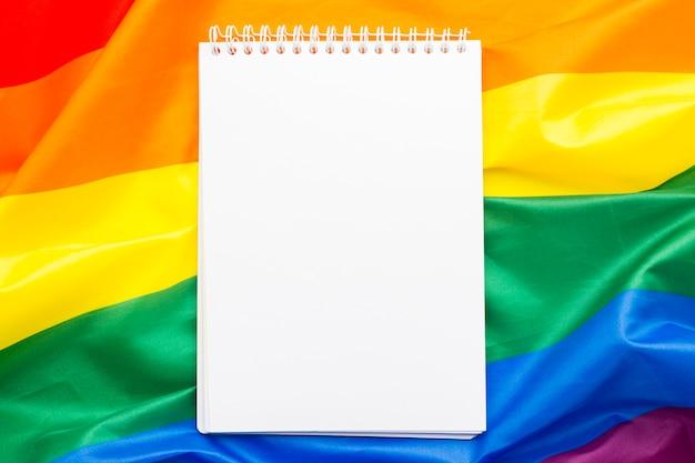 Copie o bloco de notas vazio de espaço rodeado pela bandeira do orgulho do arco-íris