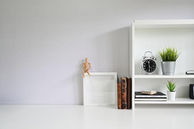 Copie o espaço com livros, alarme na mesa branca.
