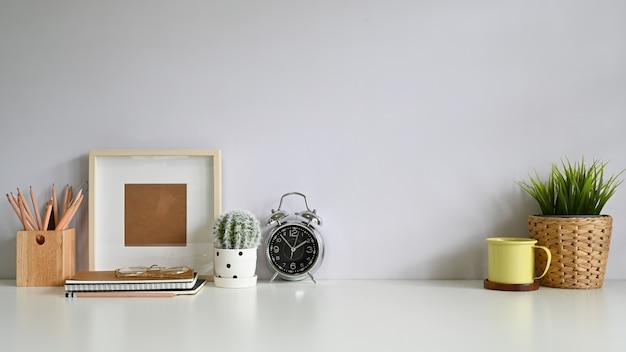 Copie o espaço de trabalho do espaço com molduras para fotos, café, decoração de plantas, lápis na mesa de escritório.