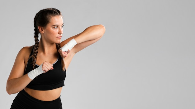 Copie o espaço e ajuste a mulher em posição de combate