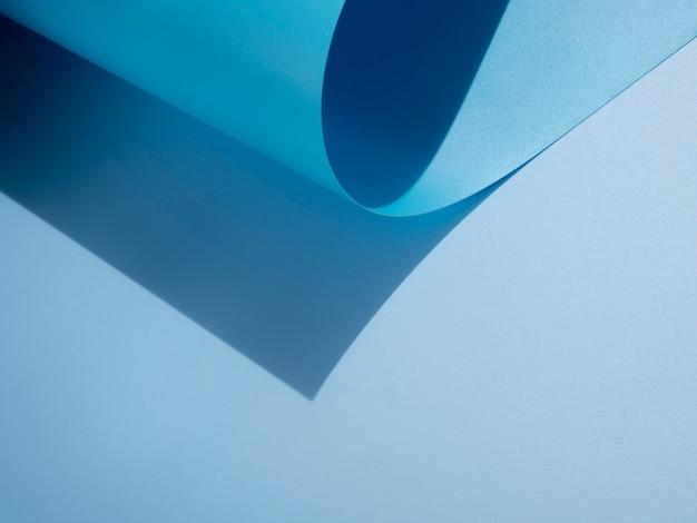 Copie o espaço e o papel monocromático curvado abstrato azul