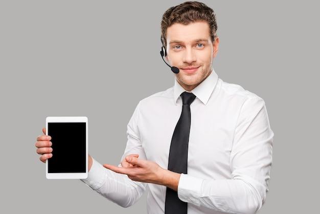Copie o espaço em seu laptop. jovem bonito em trajes formais e fone de ouvido apontando para tablet digital em pé contra um fundo cinza