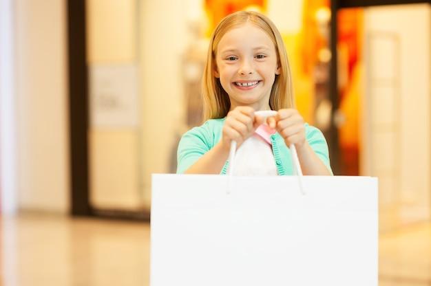 Copie o espaço em sua sacola de compras. menina alegre segurando sacola de compras e sorrindo em pé no shopping