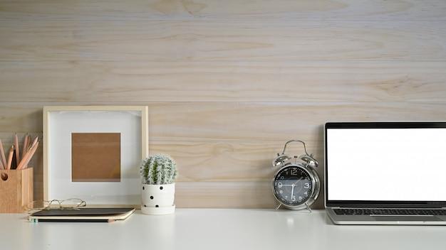 Copie o espaço espaço de trabalho maquete laptop, molduras para fotos, despertador e cacto na mesa com parede de madeira.