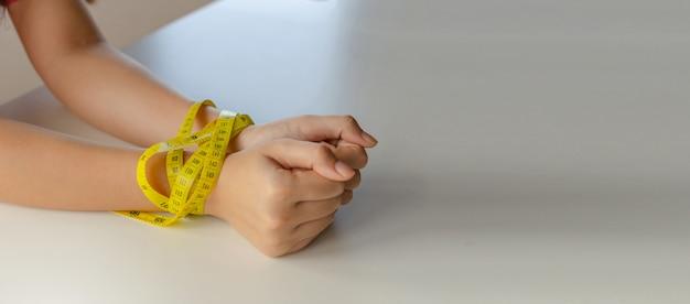 Copie o espaço. mãos de mulher jovem amarradas com fita métrica amarela para controle de peso