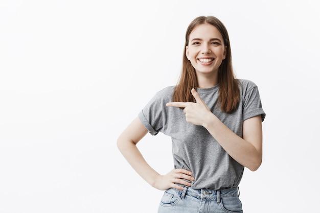 Copie o espaço para o seu anúncio. jovem morena caucasiana linda sorrindo, com uma expressão feliz, apontando um lado com o dedo na parede branca.
