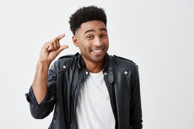 Copie o espaço para o seu anúncio. retrato isolado de alegre jovem atraente estudante do sexo masculino de pele escura com corte de cabelo afro em camiseta branca sob a jaqueta de couro gesticulando com a mão, olhando em c