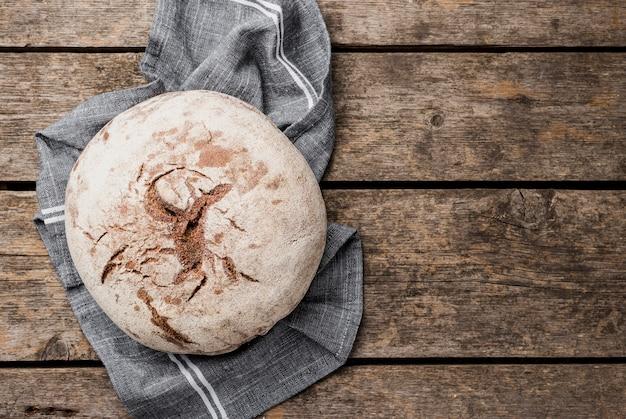 Copie o espaço redondo pão no pano e fundo de madeira