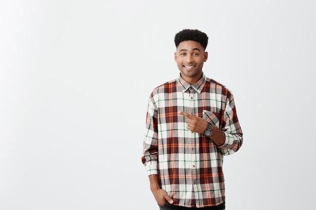 Copie o espaço. retrato de jovem atraente pele bronzeada cara alegre com penteado afro em camisa casual, sorrindo, apontando com o dedo de lado com expressão alegre e cam.