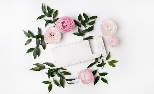 Copie o fundo do conceito de espaço com flores e uma placa de madeira isolada no branco