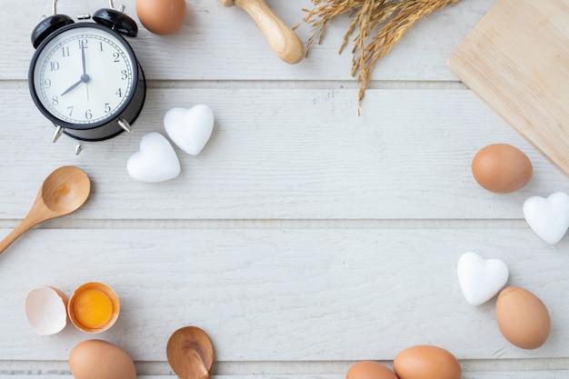 Copie o quadro do espaço para o texto na mesa de cozinha branca com os ovos crus frescos, ovos amarelos da gema.