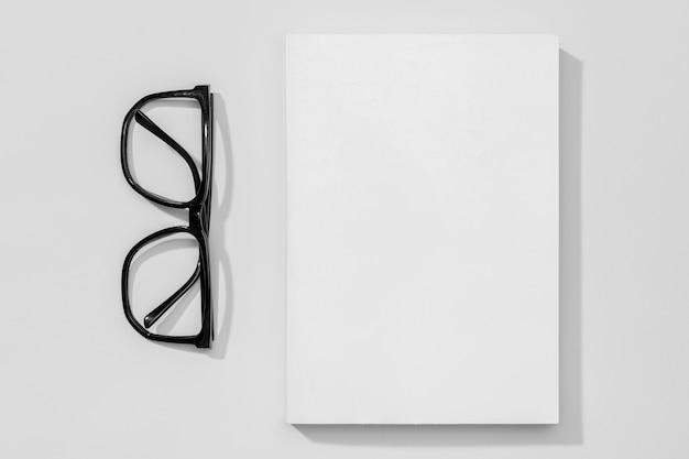 Copie páginas espaciais de livro e óculos de leitura