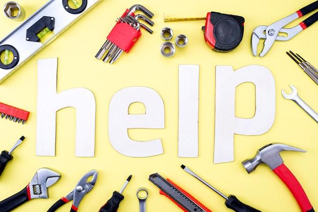 Coplet de ferramentas de reparo em uma parede amarela e a palavra ajuda feita de letras de madeira. equipamento para construção. kit de ferramentas de reparo. vista de cima