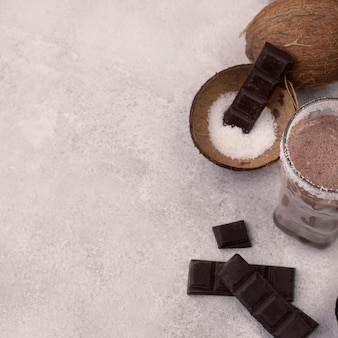 Copo alto de milkshake de chocolate com coco e espaço de cópia