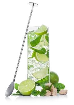 Copo alto de mojito coquetel alcoólico de verão com cubos de gelo de hortelã e lima em fundo branco com açúcar de cana e lima crua com colher longa de aço