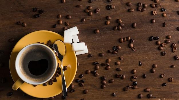Copo amarelo com placa e açúcar bloqueia perto de grãos de café