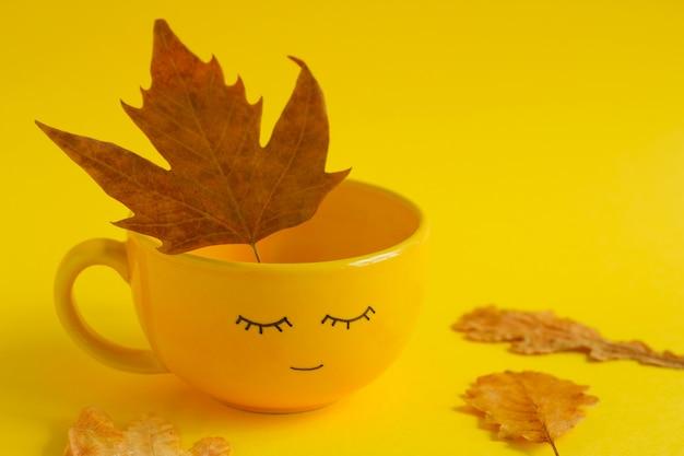 Copo amarelo com rosto sorriso fofo e maple folhas de outono secas em amarelo