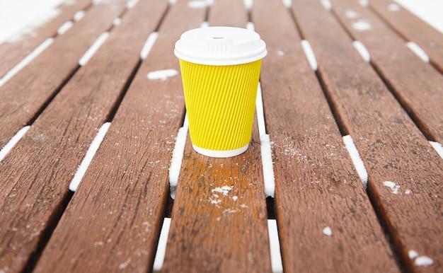 Copo amarelo para viagem com bebida quente, café ou chá em um banco de madeira em um parque de inverno nevado