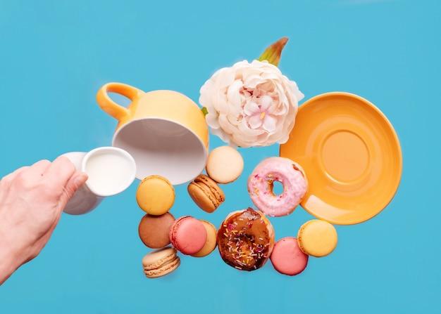 Copo amarelo vazio, donuts, biscoitos, peônia e mão segurando uma jarra de creme de leite voando sobre um fundo azul