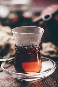 Copo armudu com chá preto com utensílios de cozinha na mesa