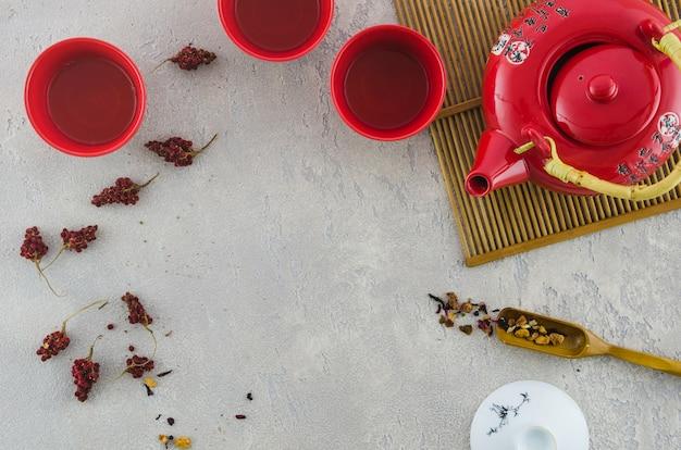 Copo asiático vermelho e bule com ervas no plano de fundo cinza texturizado