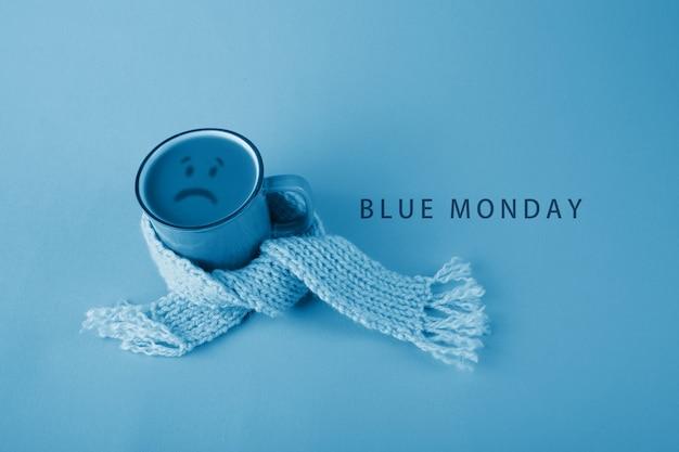 Copo azul com cachecol café sobre fundo azul. conceito de segunda feira azul