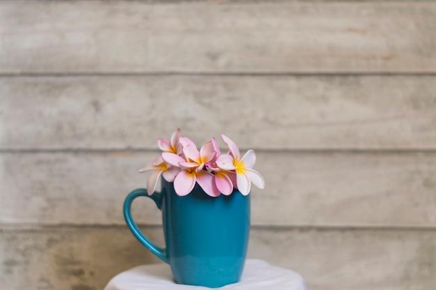 Copo azul com flores e fundo de madeira