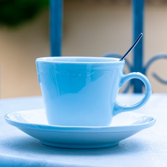 Copo azul com uma colher em cima da mesa