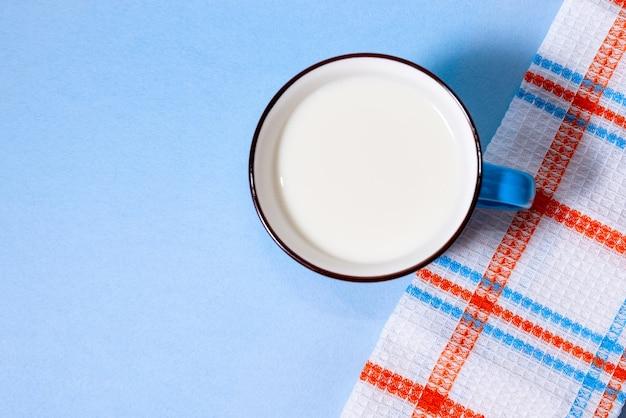 Copo azul de leite sobre fundo azul claro. vista de cima.