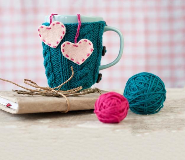 Copo azul em um suéter azul com corações de feltro