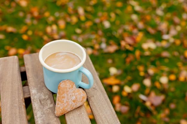 Copo azul metal com café e biscoito em uma mesa