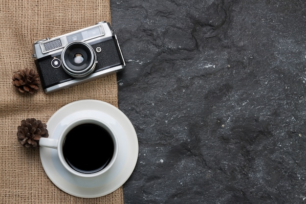 Copo branco café e câmera velha, pinho seco na serapilheira em fundo preto de pedra