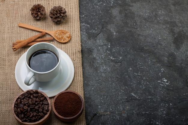 Copo branco café, grãos de café no copo de madeira, pinho na serapilheira na pedra preta texturizada