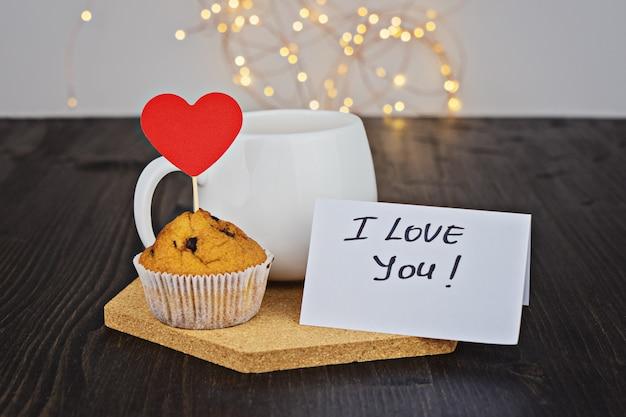 Copo branco, cartão de dia dos namorados e muffin de chocolate com corações vermelhos