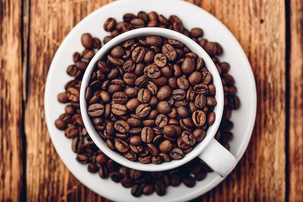 Copo branco cheio de grãos de café torrados no pires. vista de cima