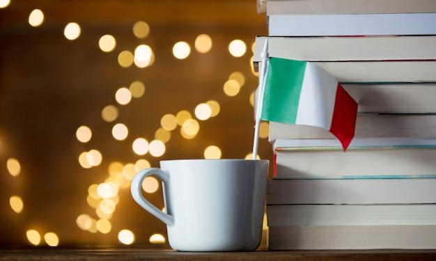 Copo branco com bandeira da itália perto de livros