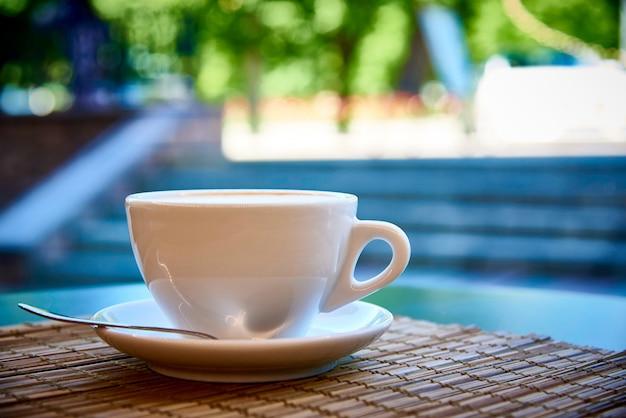 Copo branco com bebida do café no close-up de bambu do guardanapo no fundo brilhante com bokeh.