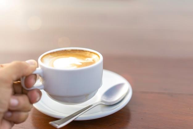 Copo branco com café com leite quente no café.