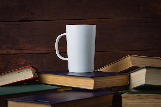 Copo branco com café quente em livros implantados em uma parede de madeira escura