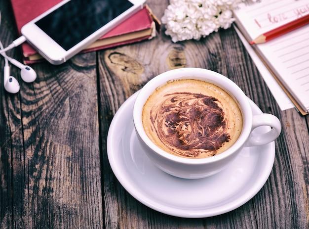 Copo branco com cappuccino atrás do telefone móvel