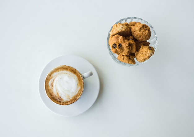 Copo branco com cappuccino e biscoito na mesa branca.
