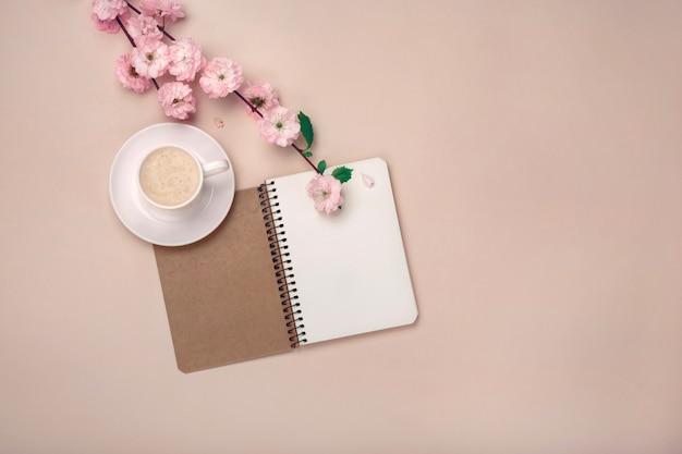 Copo branco com cappuccino, flores de sakura, caderno em rosa
