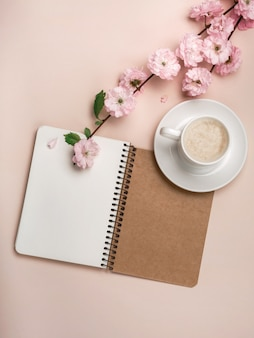Copo branco com cappuccino, flores de sakura, caderno em um fundo do rosa pastel. dia das mães